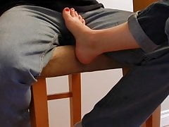 Wife teasing with her feet under table