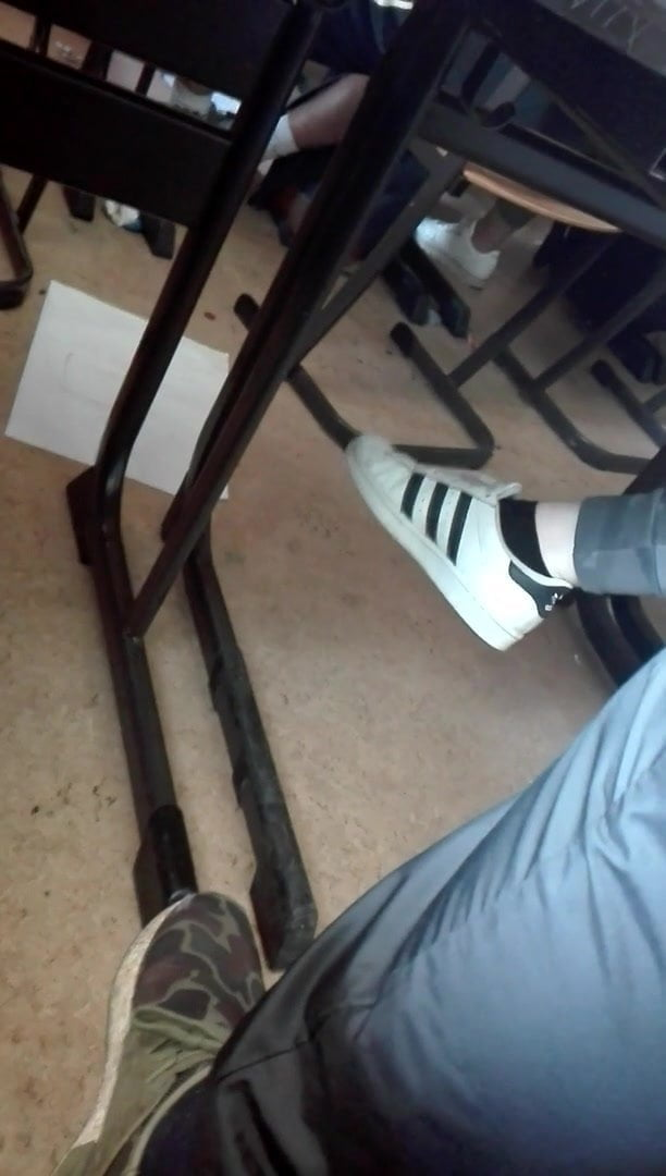 Teen dangling feet in sneakers