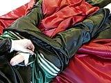 Black satin pajamas, red satin sheets, green Adidas shorts