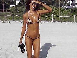在海灘上的極短的比基尼cameltoe字符串