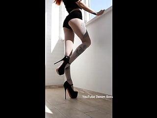 Slender legs in high heels in black shoes.Tattooed legs