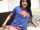 Brunette in superman t-shirt finger fucks herself on the sofa