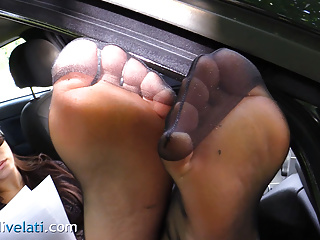 Brunette in pantyhose shows feet in the street